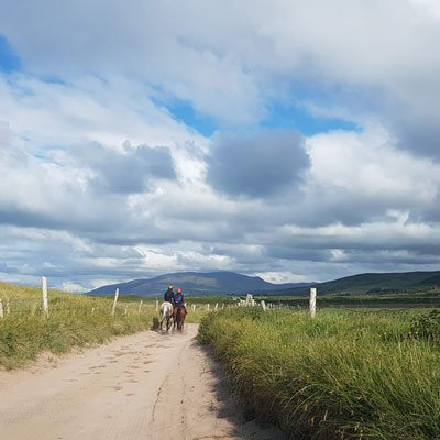two horses and riders on a sandy road with mountains behind at stradbally dingle peninsula ireland