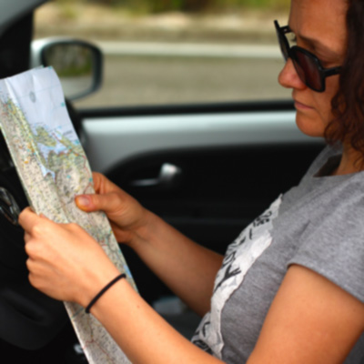 lady with sunglasses in car reading a map